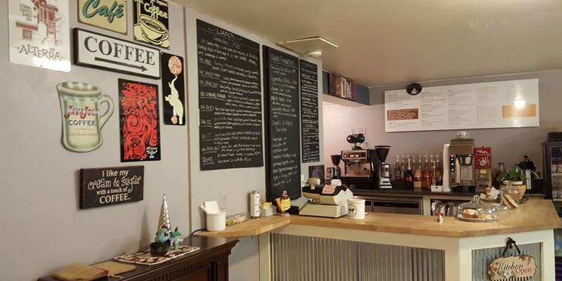 Cozy coffee place with chalkboards for messages and books for browsing.