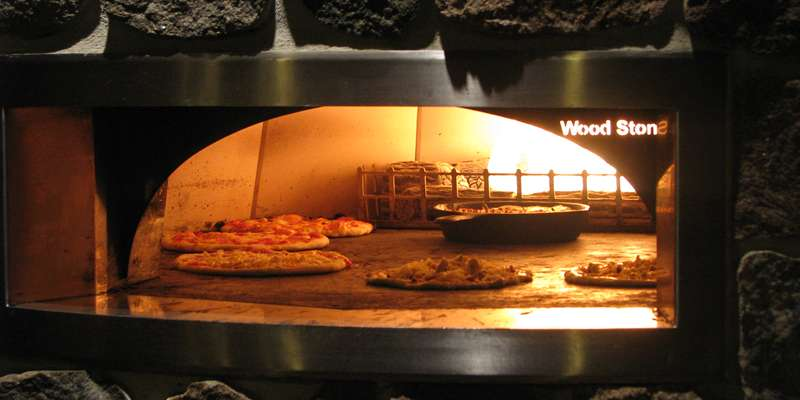 Hand made pizzas cooking in our 600 degree oven.
