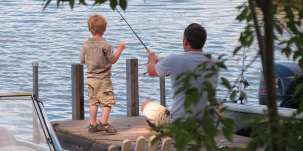 Dad and son enjoying morning fishing on the pier