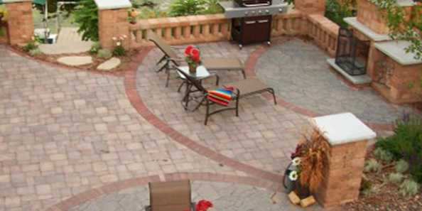 Professional hardscaped patio with fireplace, patio furniture and gas grill.