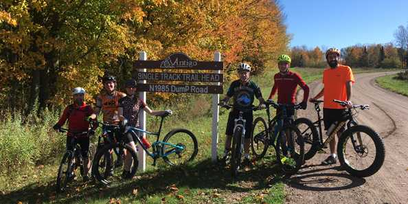 Group picture at Antigo Single Track Mountain Bike Trail Head sign.