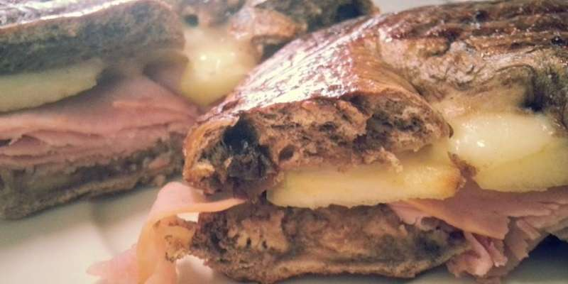 A hot ham and swiss sandwich with sliced apples and served on a cinnamon raisin bagel.