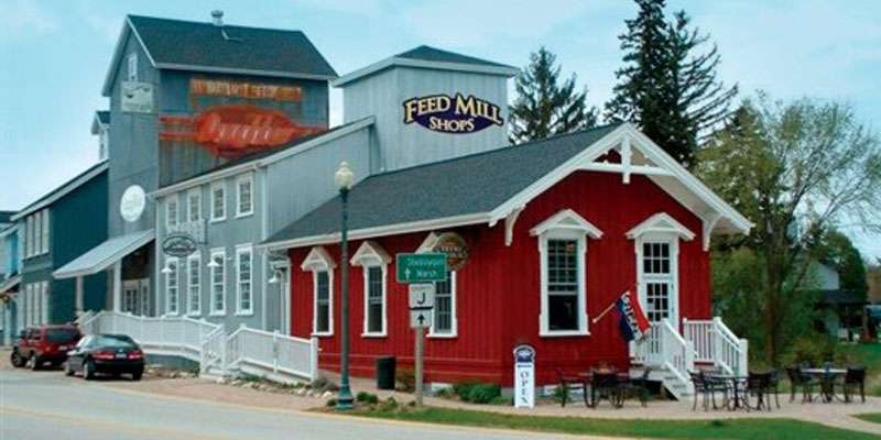 The Feed Mill Shops are located in a renovated feed mill in the center of the village square. The first (red) section is Elkhart Lake's original railroad depot which was restored and houses Off the Rail Cafe. Next in line is Gina's fine gifts and framing. The business at the far end is Elkhart Lake's home town grocery store.